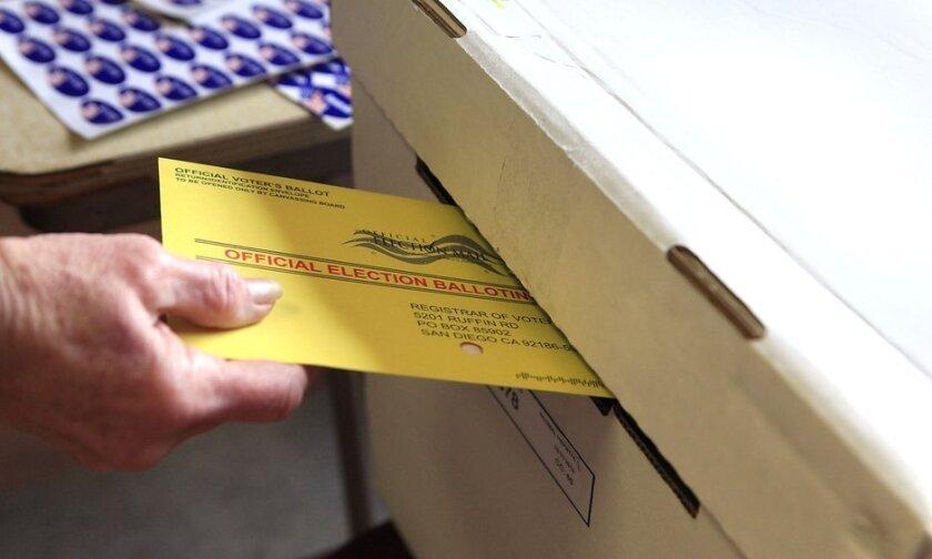 A voter slides a ballot into a ballot box.