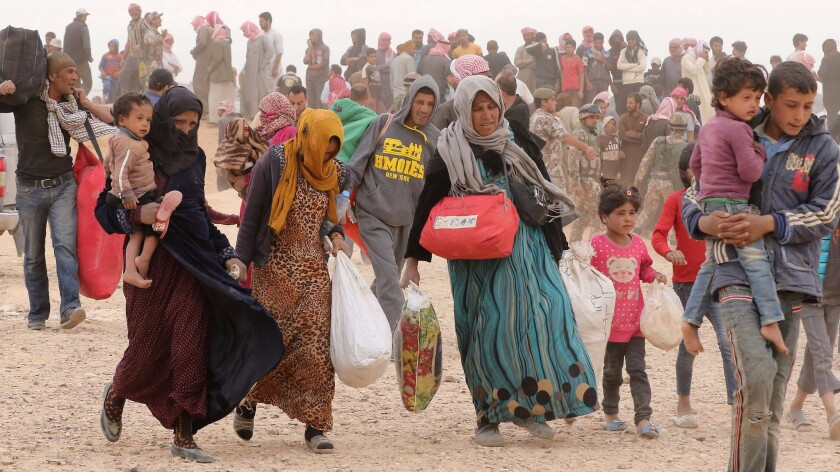 Syrian refugees carrying their belongings as they wait to enter Jordanian side of the Hadalat border crossing.
