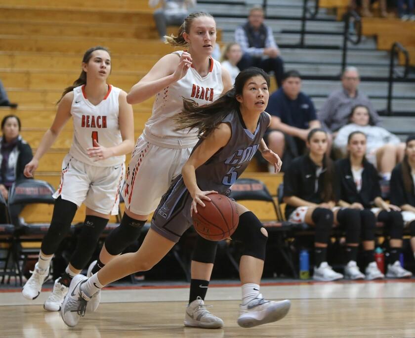 Corona del Mar's Samantha Uehara drives to the basket for a score around Huntington's Andie Payne du