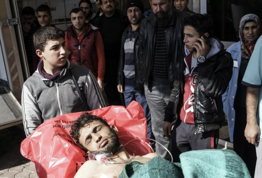 FILE - In this Feb. 15, 2016 file photo, a wounded Syrian man is carried to a hospital in Kilis, Turkey. The fighting in northern Syria has huge implications in the civil war and risks erupting into a wider regional conflict. The battle for control of Aleppo involves all the major players over a pr