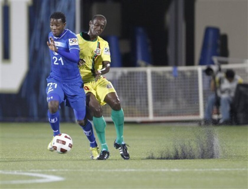 Honduras' Juan Carlos Garcia, left, and Grenada's Ricky Charles battle for the ball in the first half of a CONCACAF Gold Cup soccer match, Friday, June 10, 2011, in Miami.(AP Photo/J Pat Carter)
