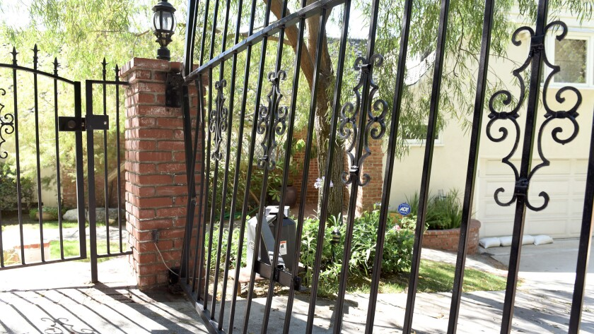 A black metal gate that blocks Anton Yelchin's sloping driveway appears bent and damaged on June 19.