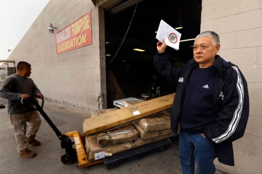 Cliff Chih, 58, an opponent of the marijuana production development, stands next to the warehouse that is slated to house the facility. Chih said a relative is addicted to the substance, and he worries about other young people.