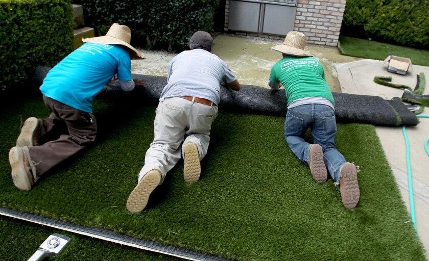 Workers install artificial turf