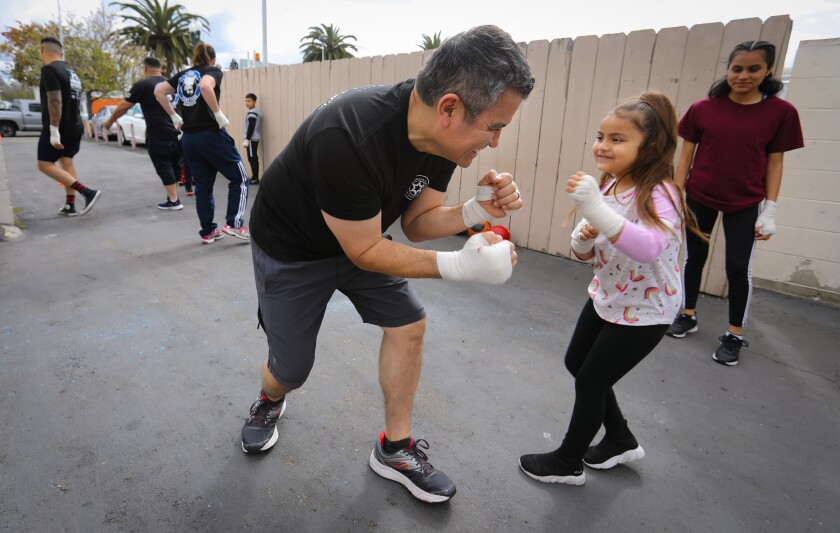 """Lt. Antonio Ybarra of the National City Police Department shadowboxes with Sophia Jimenez, 6, while Emily Serapio, 14, watches. Saturday was National City's first """"Box With a Cop"""" event."""