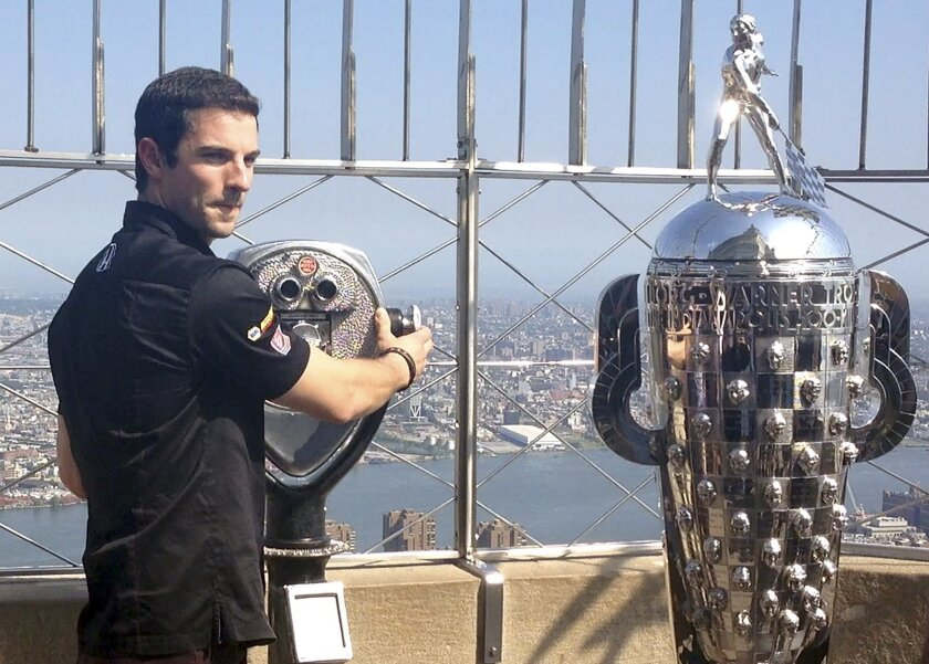 In this image taken from video, Alexander Rossi, winner of the Indianapolis 500 auto race, poses with the Borg-Warner Trophy, on the observation deck of the Empire State Building in New York. (AP Photo/Rachel Cohen)