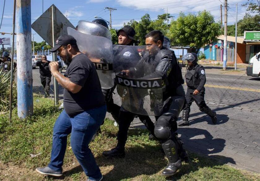 Agentes de la policía nacional repliegan al periodista Nestor Arce del semanario Confidencial al llegar a la sede central de la policía a pedir explicaciones sobre el allanamiento del medio de comunicación, en Managua (Nicaragua). EFE/Archivo