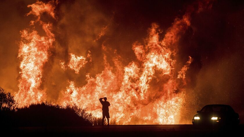 FILE - In this Dec. 6, 2017, file photo, a motorist on Highway 101 watches flames from the Thomas Fi