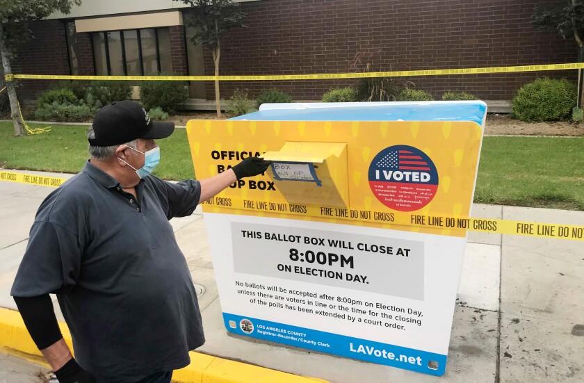Baldwin Park resident John Rios examines the ballot box that was burned.