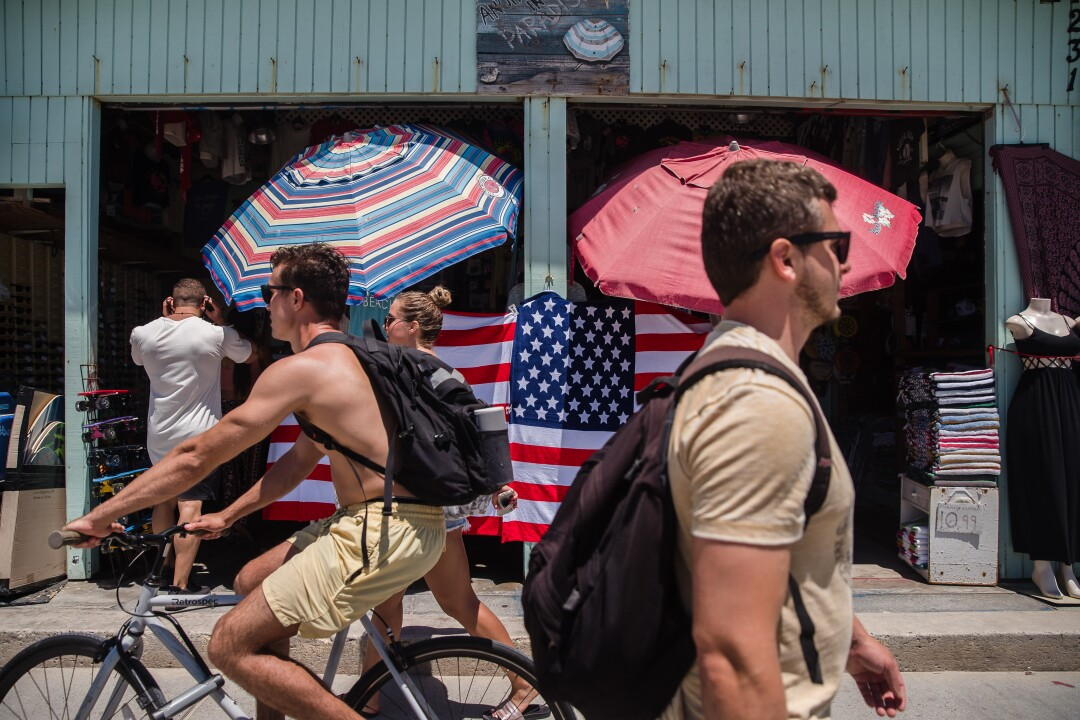 People walk along the boardwalk on July 5 in Pacific Beach.