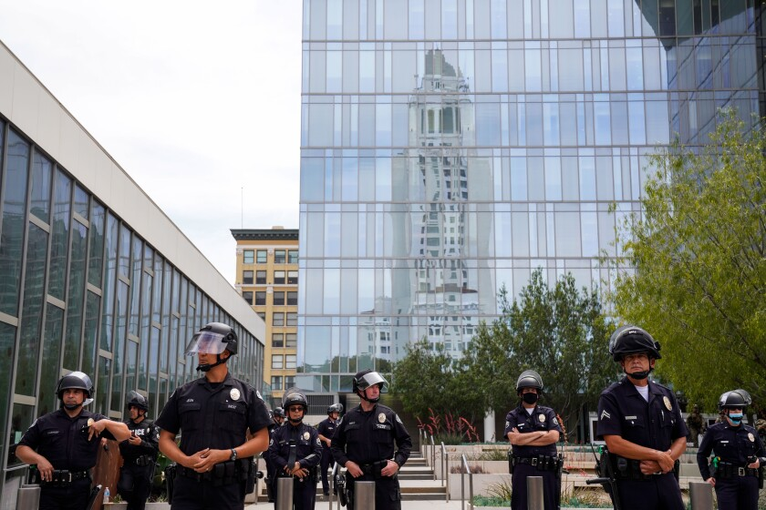 LAPD officers outside their headquarters  as demonstrators gather  Tuesday.