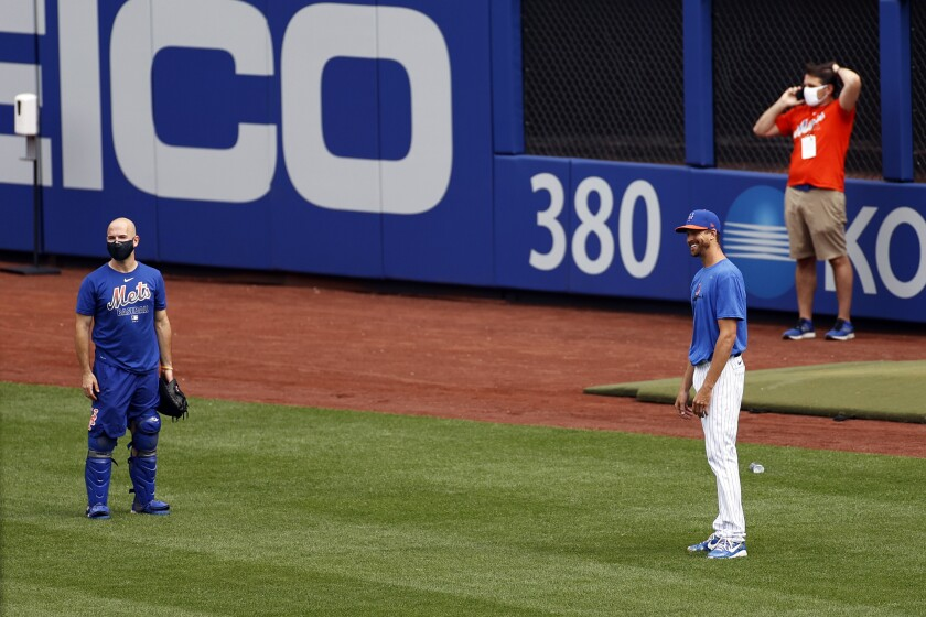 New York Mets pitcher Jacob deGrom, right, laughs during a baseball workout at Citi Field in New York, Friday, July 3, 2020. (AP Photo/Adam Hunger)