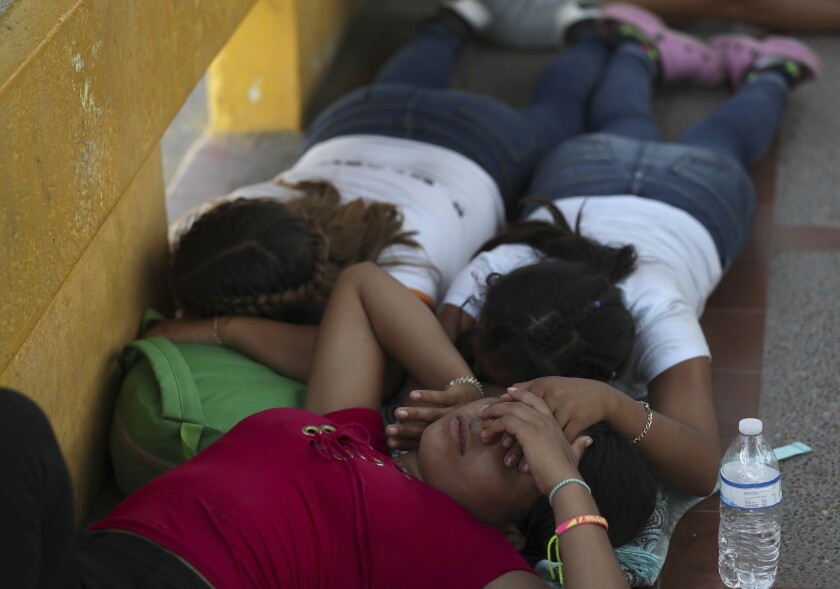 Migrant women sleep after camping out on the Gateway International Bridge that connects downtown Matamoros, Mexico with Brownsville, Thursday, Oct. 10, 2019. Migrants wanting to request asylum camped out on the international bridge leading from Mexico into Brownsville, Texas, causing a closure of the span. (AP Photo/Fernando Llano)