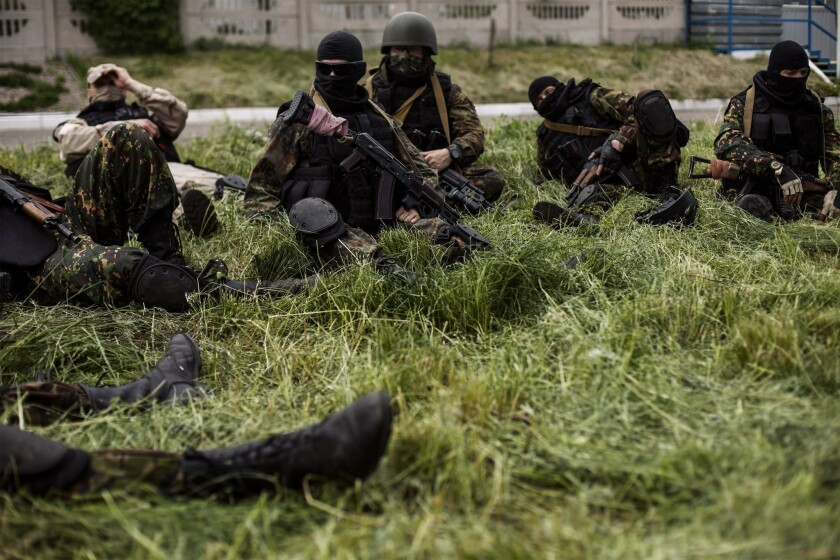 Pro-Russia gunmen in the eastern areas of Ukraine rest at a checkpoint in the village of Pisky, near Donetsk, two days before the nation's presidential election.