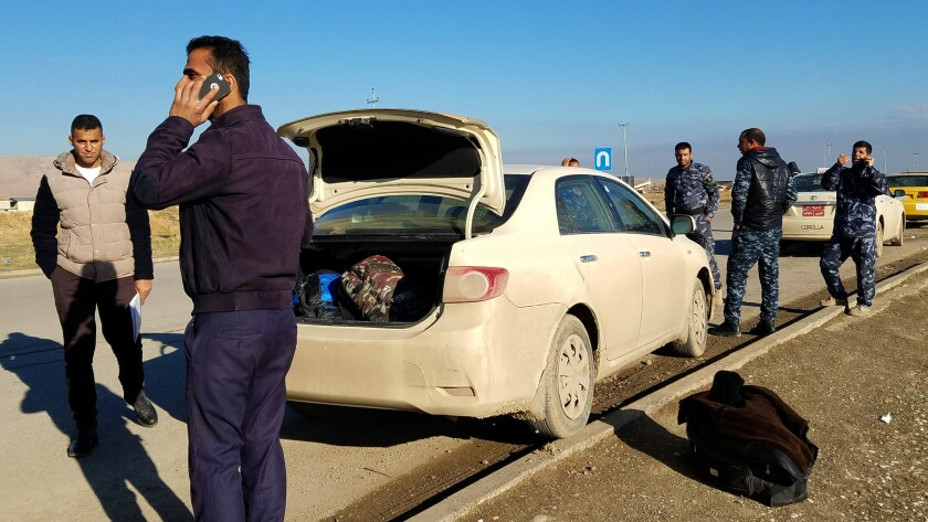 Hoshyar Faisal Qasim talks on his cellphone as he waits for fares near an Iraqi security forces checkpoint east of Mosul.