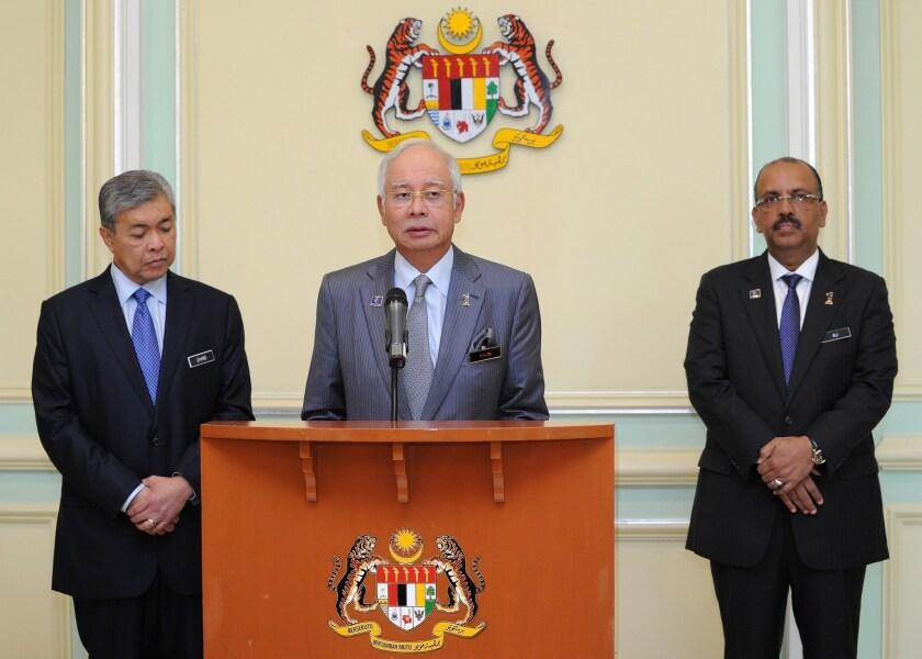 Malaysia's Prime Minister Najib Razak addresses a news conference in Putrajaya as newly appointed Deputy Prime Minister Ahmad Zahid Hamidi, left, and Malaysia's Chief Secretary Ali Hamsa listen.