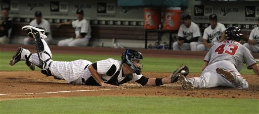Washington Nationals runner Rick Ankiel (43) slides past Florida Marlins catcher John Buck while scoring on a Ivan Rodriguez single during the second inning of a baseball game in Miami, Wednesday, April 6, 2011. (AP Photo/J Pat Carter)