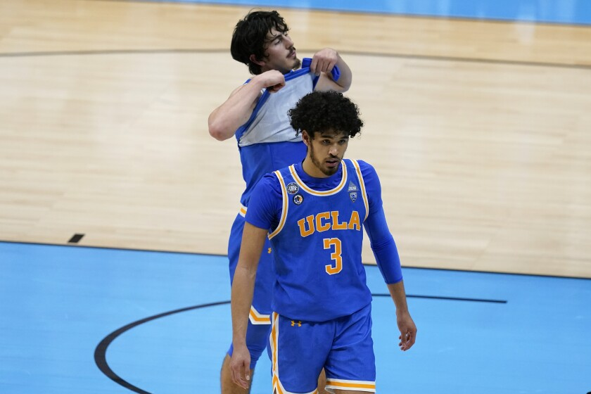 UCLA's Johnny Juzang and Jaime Jaquez Jr. walk off the court after losing to Gonzaga on a last-second shot in overtime.
