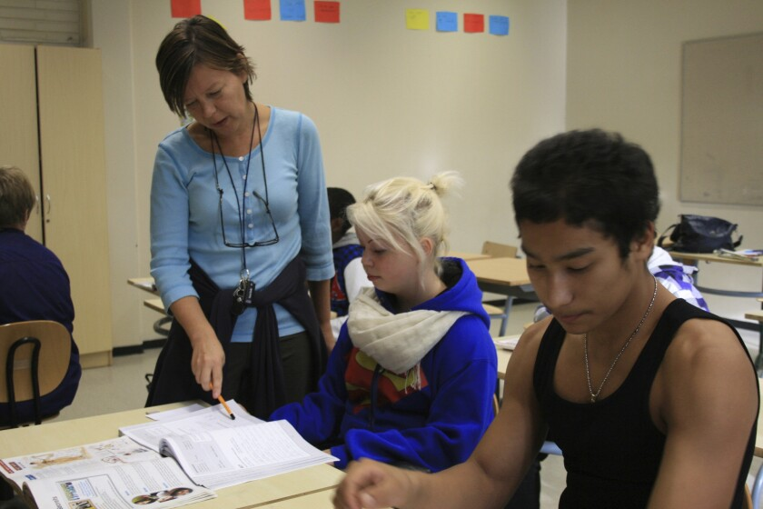 A teacher works with seventh-grade students at a school in Helsinki, Finland in 2011.