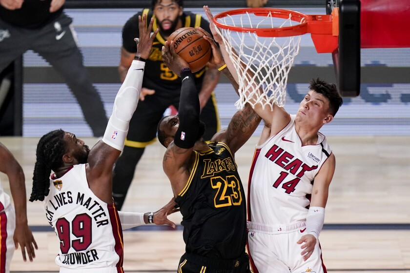 Los Angeles Lakers forward LeBron James scores between Miami Heat forward Jae Crowder, left, and guard Tyler Herro.