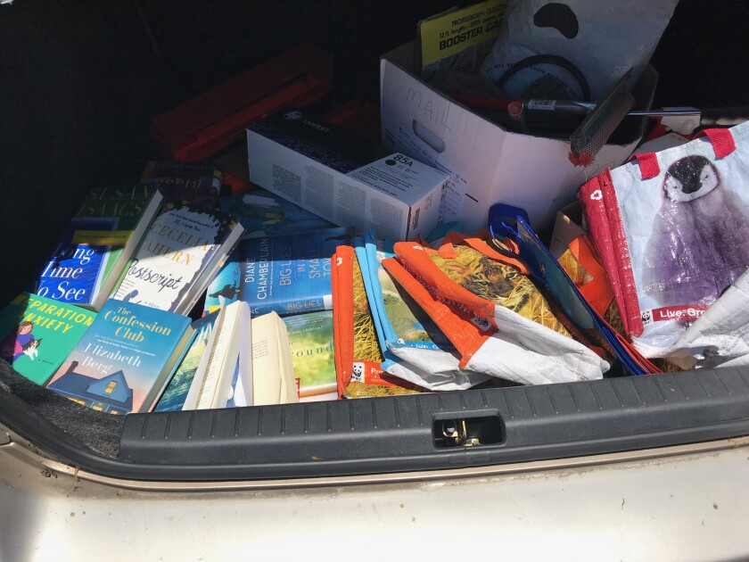 Inga's car trunk is seen filled with unreturnable library books, unrecyclable printer cartridges and unusable shopping bags.