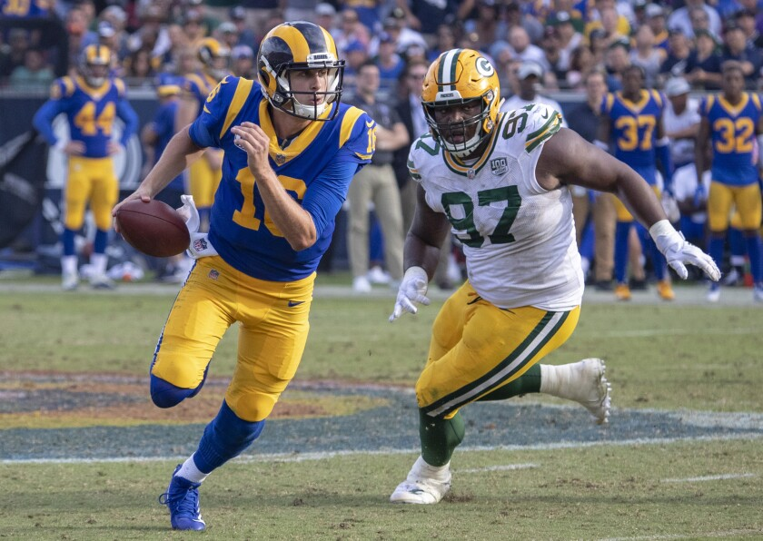 Rams quarterback Jared Goff scrambles from the pressure of Packers defensive lineman Kenny Clark on Sunday.