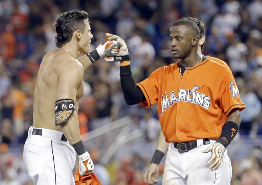 Miami Marlins' Derek Dietrich, left, is congratulated by teammate Adeiny Hechavarria after hitting a winning triple against the St. Louis Cardinals in the ninth inning of a baseball game, Sunday, July 31, 2016, in Miami. Hechavarria scored on the triple. (AP Photo/Alan Diaz)
