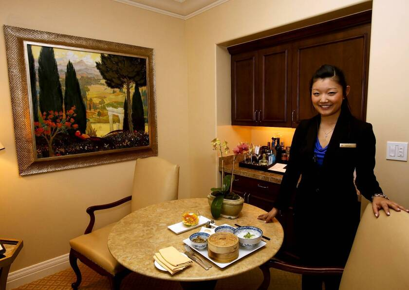 Tiffany Li, a guest relations agent at the Montage Beverly Hills, displays a traditional Chinese breakfast in one of the suites. The hotel is adding services and extras to draw Chinese tourists.