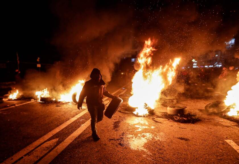 An anti-government protester carries a tyre to be set aflame as a section of the Beirut-Byblos highway is cut off in Byblos on January 21, 2020, as they protest the newly-announced government formed by Prime Minister Hassan Diab.