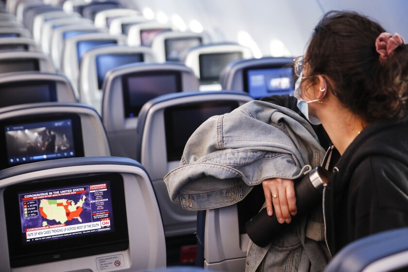 A passenger wears personal protective equipment on a Delta Airlines flight as a map depicting the spread of COVID-19 is displayed on a monitor after landing at Minneapolis−Saint Paul International Airport, Thursday, May 28, 2020, in Minneapolis. (AP Photo/John Minchillo)