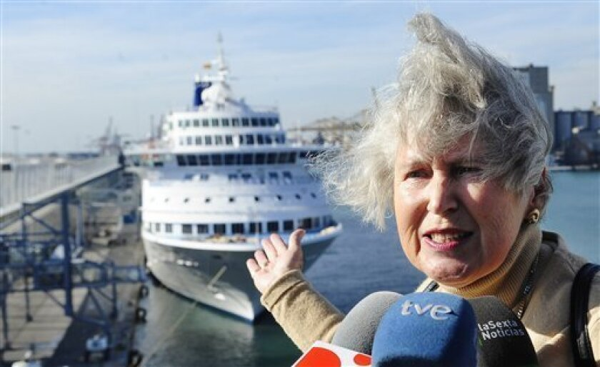 Passenger Margit Kohe Ternes of Germany talks to reporters after getting off the Cypriot-owned Louis Majesty cruise ship, background, at Barcelona's port, Spain, on Thursday, March 4, 2010. Waves of up to 26 feet (8 meters) high smashed into the Mediterranean cruise ship flooding people's cabins and breaking windows in an ordeal that claimed two lives. The ship was carrying 1,350 passengers and 580 crew. (AP Photo/Manu Fernandez)