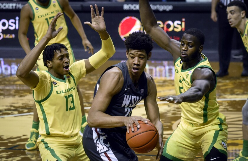 Oregon forwards Chandler Lawson (13) and Eugene Omoruyi (2) pressure Washington State center Dishon Jackson (21) during the first half of an NCAA college basketball game Thursday, Feb. 4, 2021, in Eugene, Ore. (AP Photo/Andy Nelson)