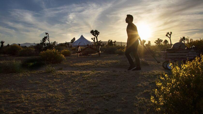 JOSHUA TREE, CA - MAY 15, 2018: Jose Sanchez-Castro of Pasadena pulls his luggage in a wagon along
