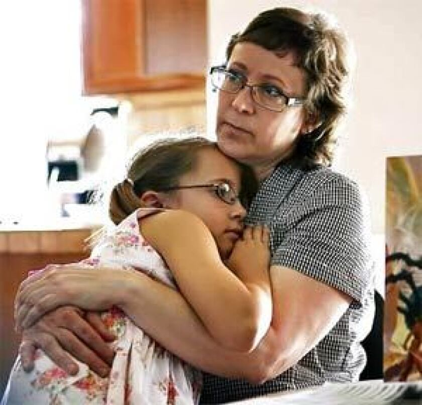 Leslie Udvardi snuggles with her daughter, Esther, as the family plays board games in July 2007. Esther and her three brothers were taken from Leslie and her husband, Kirk, after she was accused of having Munchausen syndrome by proxy in December 2005.