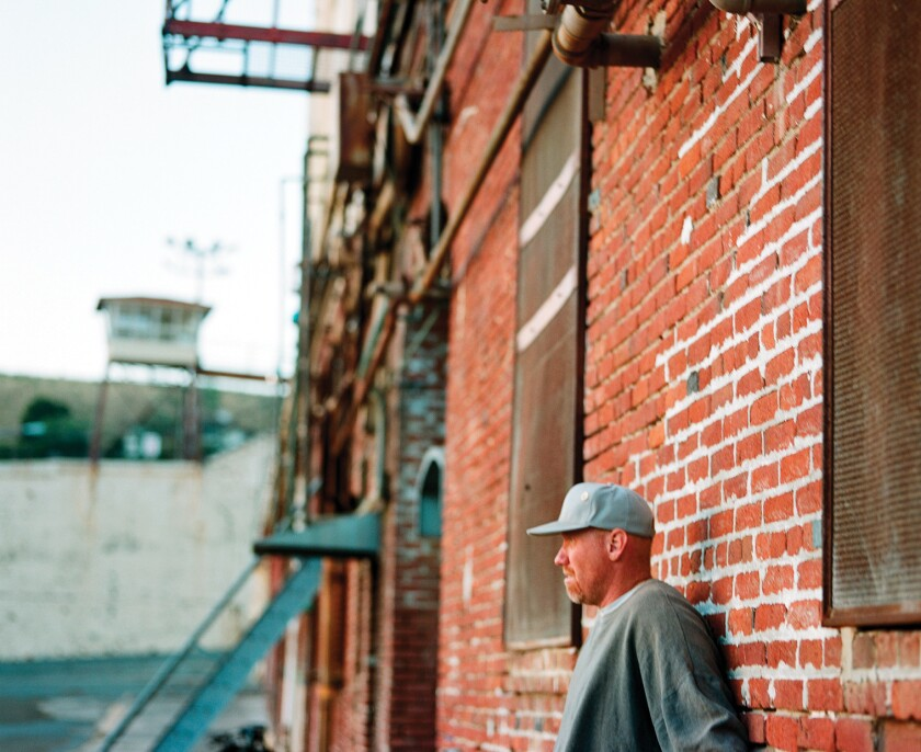 """An inmate named Mike Bjorlin looks out over the yard at San Quentin State Prison in Northern California. The image is from Heather Rowley's 2008 book """"Is It Safe? Essays and Photographs of Students in the San Quentin College Program."""""""