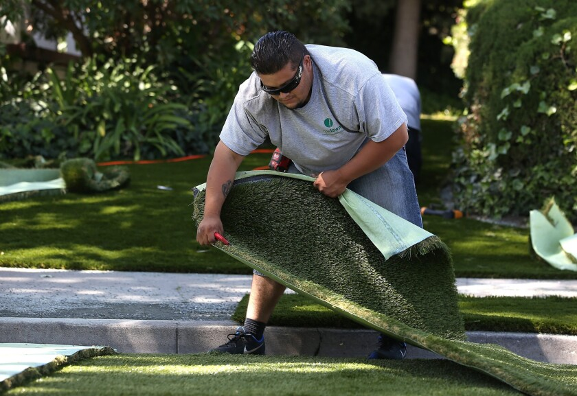 Juan Martinez of landscaping company Onelawn installs a section of artificial lawn at a home in Burlingame, Calif.