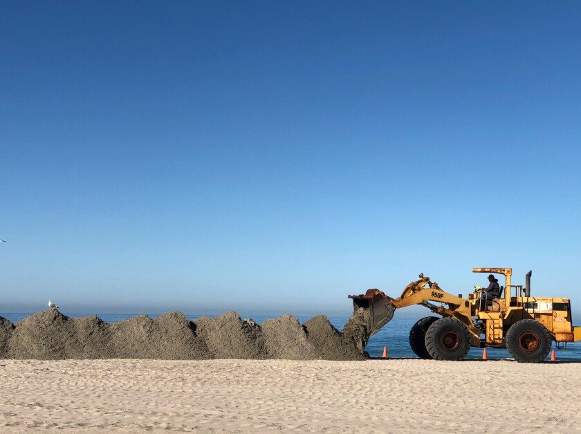 Workers dumped about 500 to 700 cubic yards of sand onto Moonlight Beach, part of sand replenishment efforts.