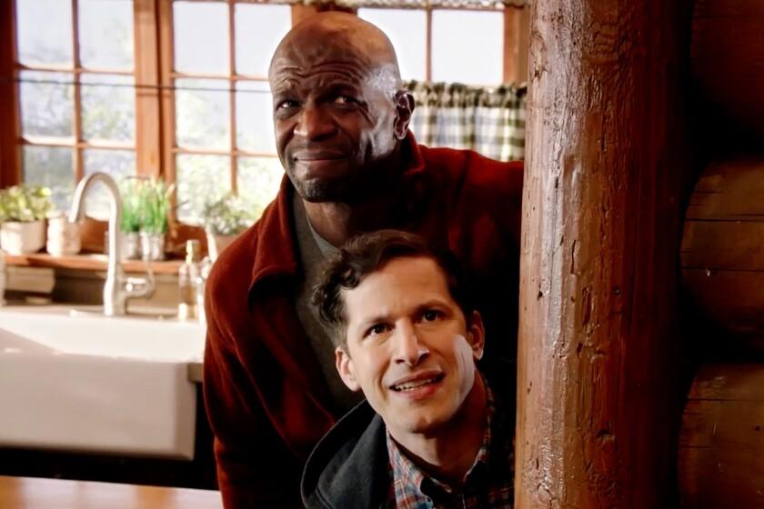 """Terry Crews stands behind Andy Samberg in a doorway in """"Brooklyn Nine-Nine"""" on NBC."""