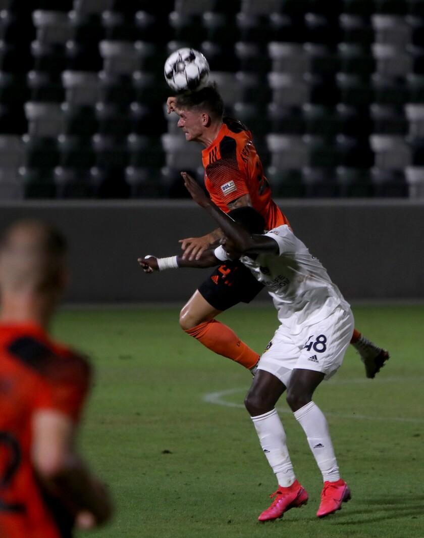 El defensa del Orange County Soccer Club Rob Kiernan, arriba, cabecea el balón contra el delantero del LA Galaxy II, Augustine Williams.