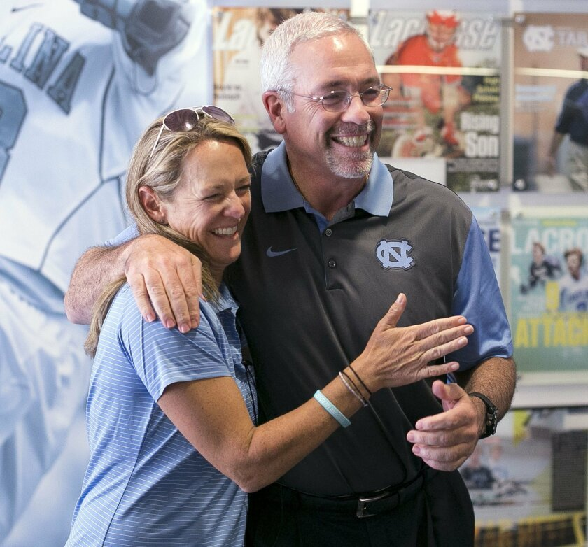 North Carolina men's lacrosse coach Joe Breschi embraces North Carolina women's lacrosse coach Jenny Levy before entering a press conference together where both coaches talked about winning dual NCAA National Championships on Tuesday, May 31, 2016 at Kenan Stadium in Chapel Hill, N.C. Both lacrosse
