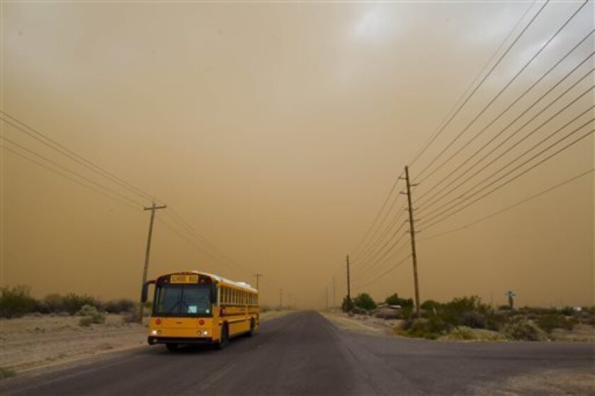 A school bus emerges from a dust storm in Casa Grande, Ariz. on Wednesday, July 10, 2013. (AP Photo/The Arizona Republic, Patrick Breen) MARICOPA COUNTY OUT; MAGS OUT; NO SALES