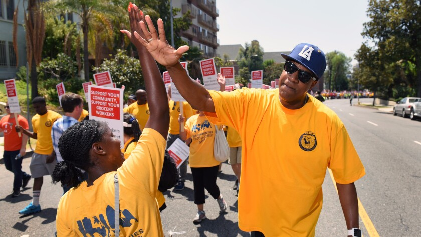 Gerald Gates, a worker at Pavilions market in Burbank, high-fives union representative Samantha Christian as they march with grocery workers and supporters on Aug. 2 through Los Angeles to demand a new contract.