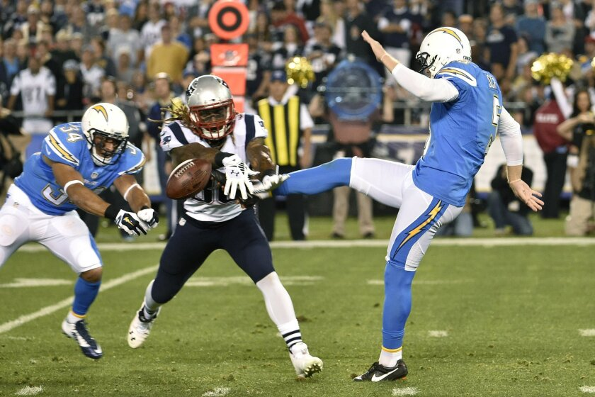 San Diego Chargers punter Mike Scifres is hit as he punts by New England Patriots'  Brandon Bolden during the first half in an NFL football game Sunday, Dec. 7, 2014, in San Diego. (AP Photo/Denis Poroy)