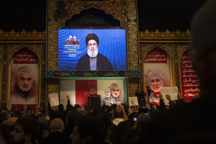 """Supporters of Hezbollah leader Sayyed Hassan Nasrallah chant slogans as he makes televised remarks at a rally in a southern suburb of Beirut, Lebanon, Sunday, Jan. 5, 2020 following the U.S. airstrike in Iraq that killed Iranian Revolutionary Guard Gen. Qassem Soleimani, seen on a poster at left, and Iraqi Popular Mobilization forces commander Abu Mahdi al-Muhandis, who was also killed. Nasrallah called the killing of Soleimani a """"clear, blatant crime"""" that will transform the Middle East. (AP Photo/Maya Alleruzzo)"""