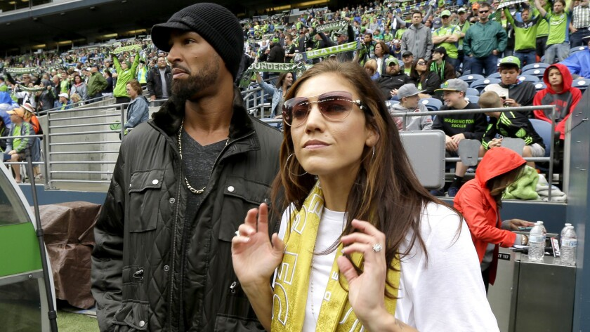Hope Solo and husband Jerramy Stevens watch an MLS game between the Seattle Sounders and Portland Timbers in Seattle on Aug. 30.