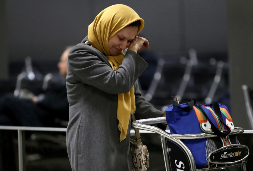 A woman traveling on a flight from Addis Ababa, Ethiopia wipes away a tear after greeting a relative in the international arrivals area of Dulles International airport on Feb. 6, 2017.