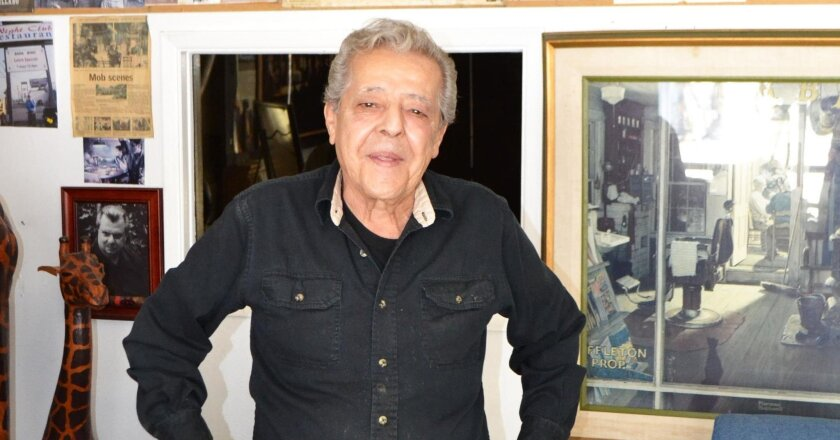 Sal Mangiavillano, owner of Poway Barber and Styling Shop, in front of some of his photos and mementos of his life, which cover the walls of his shop.