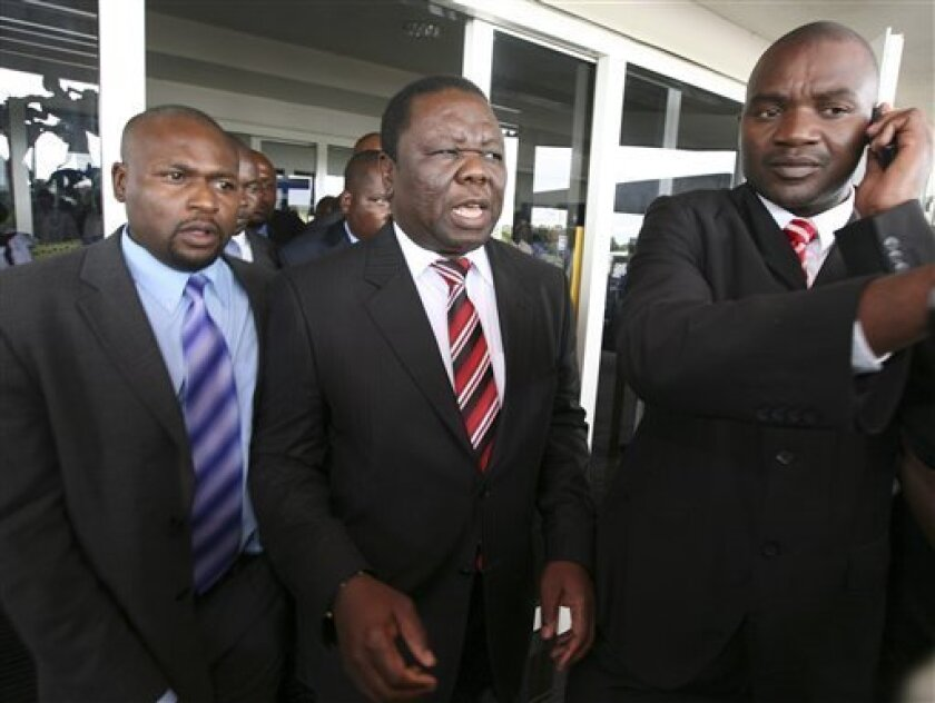 Morgan Tsvangirai, centre, leader of the main opposition party in Zimbabwe is flanked by bodyguards upon his arrival at Harare International Airport, Saturday, Jan. 17, 2009.  Tsvangirai said he was still committed participating in talks aimed at ending the Zimbabwean crisis, but vowing that he wou
