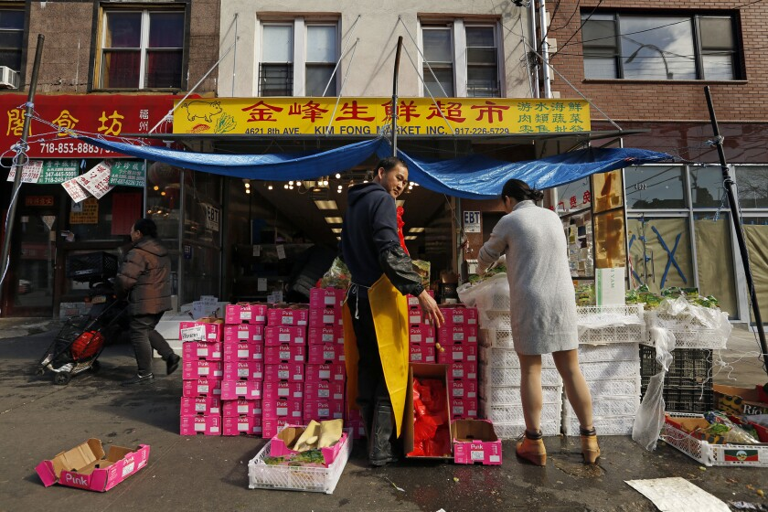 SUNSET PARK, NEW YORK--APRIL 4, 2018--Workers at Kim Fong Market on 8th Ave. in Sunset Park unpack b