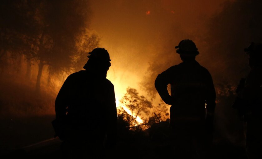 Firefighters watch as the flames of the Butte Fire approach a containment line near San Andreas, Calif. in September 2015.